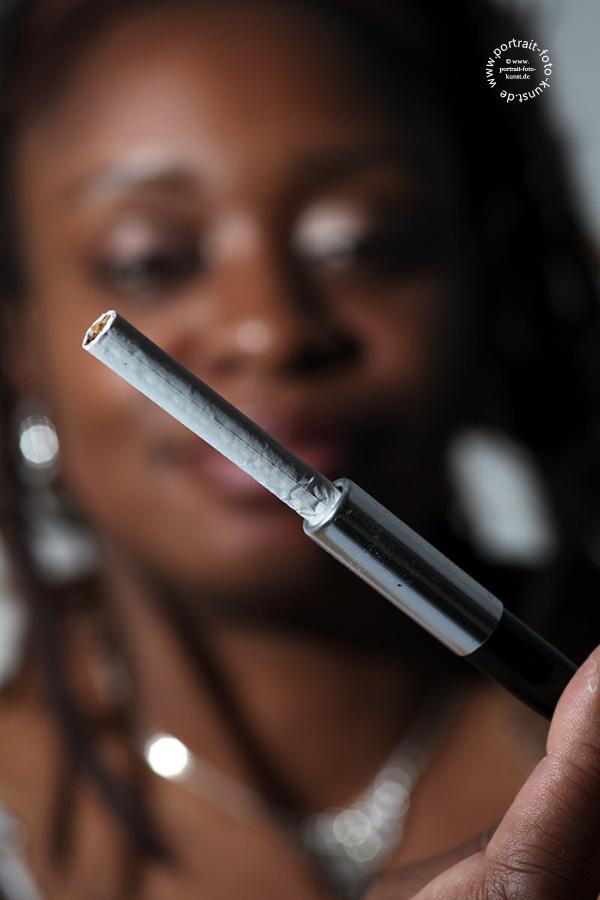 """Ein Portraitfoto bei dem die Schärfe nicht auf den Augen liegt, sondern auf der Zigarette. Es wird gegen die Regel verstoßen """"die Schärfe muß auf den Augen liegen"""""""
